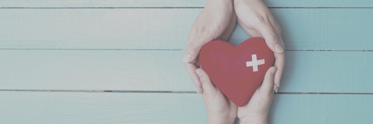 Dos pares de manos sosteniendo un corazón.